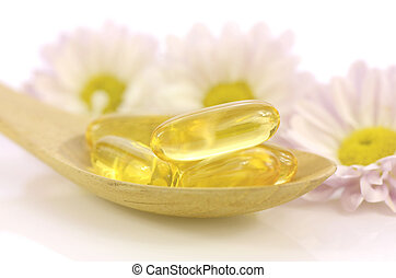 Soft gelatin capsules of dietary supplement in warm light...