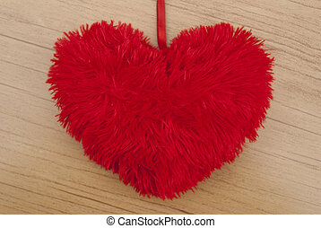 Soft red heart on a wooden background