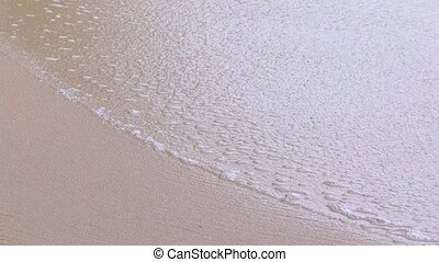 Soft Sea Foam Washes over Beach Sand