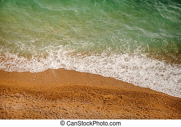 Soft sea wave on a sandy beach and pebble beach
