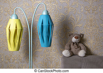 soft toy bear sits on the back of the sofa next to a vintage floor lamp