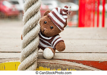 Soft toy bear sitting on the playground