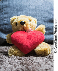 Soft toy fluffy bear with a heart sitting on the carpet