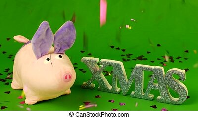 Soft toy pig stands on hromakey and the inscription XMAS,...