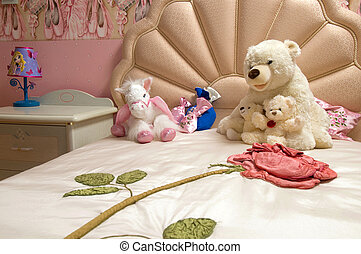 soft toys for the children lie on the bed