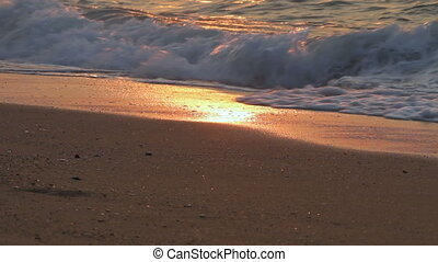 Soft wave of the sea on sandy beach. Nature background on sunset. Thailand.
