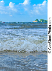 soft wave on a beach with white clouds in the sky