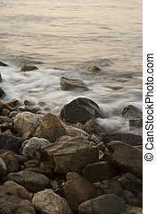 Soft waves on a rocky beach in the morning