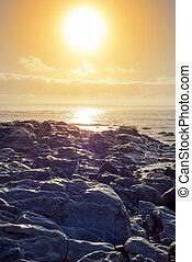 soft waves over sunset rocks