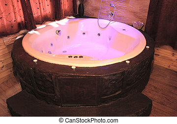 A softly lit jacuzzi hot tub in a romantic wood cabin