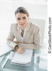 Softly smiling businesswoman writing on a clipboard looking at camera sitting at her desk