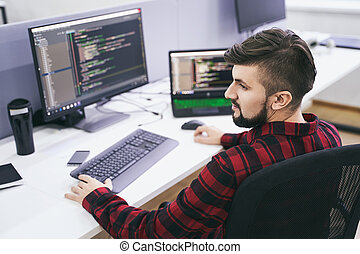 Software developer working on computer in IT office, sitting at desk and coding, working on a project in software development company or technology startup. High quality image.