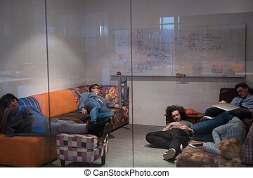 software developers sleeping on sofa in creative startup ...