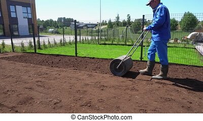 Soil compaction roller manually after seeding sow lawn in ...