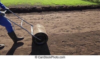 Soil compaction with roller after seeding lawn in yard. ...