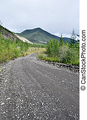 Soil highway in Yakutia. Cloudy landscape on a route Yakutsk...