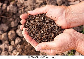Female hands full of soil over soil background. Representing fertility
