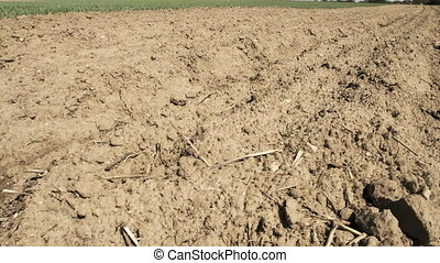 Camera slide over soil on empty field at the beginning of spring