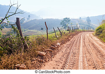 Countryside Soil road Through hills and fields.