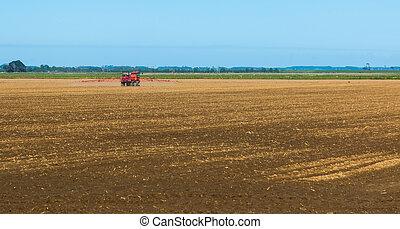 Soil Sprayer - Large spraying machine spraying on a field...
