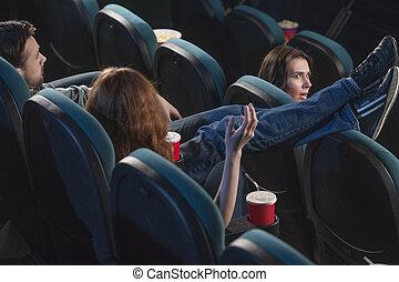 soin, sur, hommes, film regardant, anyone., jeune, siège, pieds, quoique, sien, cinéma, tenue, don?t, vue postérieure