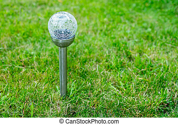 Solar cell lamp in garden and save energy of electric and save my world,close up.Charging solar lamp on the ground in the garden at sunny day, renewable energy concept.decorative spot light
