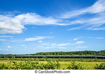 Solar cell park on a green field with blue sky