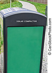 This vertical stock image is a green solar compactor, a new technology for environmental concerns in the city. These use the sun's rays for reducing waste in an ecologically friendly method.