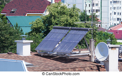 Solar energy collectors for heating the house stand on the roof