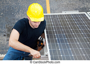 Electrician installs solar panels on the side of a building.