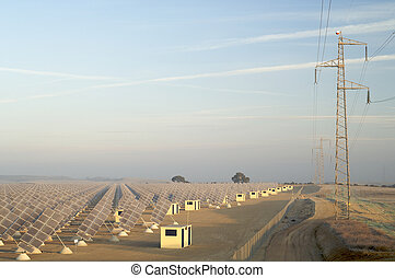 sunrise on a large group of photovoltaic panels and a power line