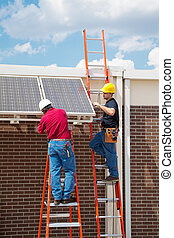 Solar Energy Installation - Two workers installing solar...
