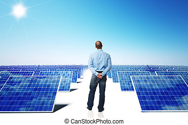 solar energy - lots of solar panel and blue sky with man...