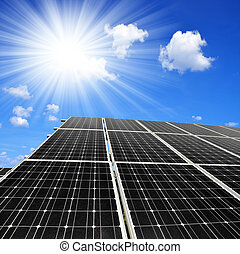 Solar energy panels against sunny sky with clouds