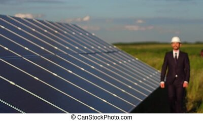 Solar energy station, satisfied business client walking and looking at solar panels.