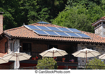 Solar hot water glass panel array on Spanish cafe roof