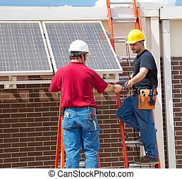Solar Panel Installation - Two electricians installing solar...