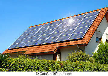 Solar panel on a red roof reflecting the sun and the...