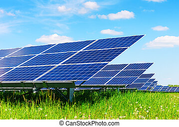 Solar panel on blue sky background. Green grass and cloudy...