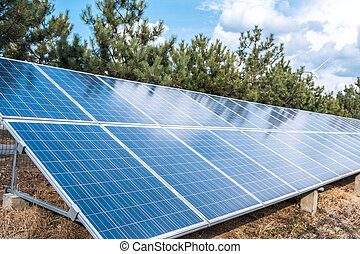 solar panel over a blue sky and green trees. ecological alternative energy