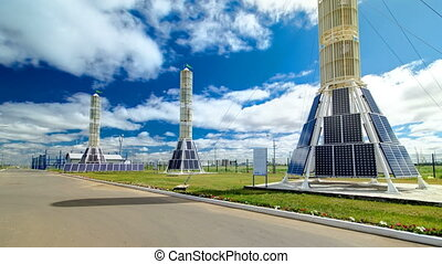 Solar Panel towers on solar plant with High Voltage Tower in...