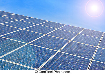 Solar panel with bright sun on blue sky