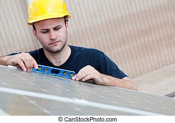 Worker installing solar panels uses a level to check that the angle is right.