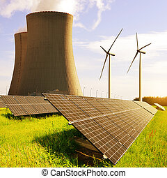 Solar panels, nuclear power plant and wind turbines at sunrise.