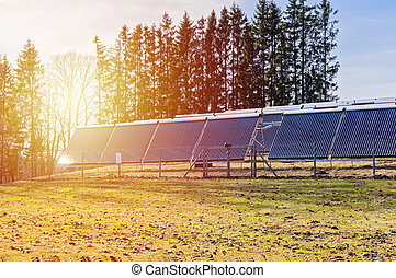 Solar panels on field in rays of sunset
