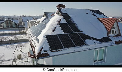 Solar panels on the roof of the house after a heavy snowfall in the winter. Renewable energy production modules. Top view