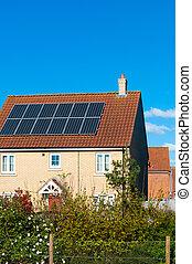 Solar photovoltaic panel array on house roof against a blue sky