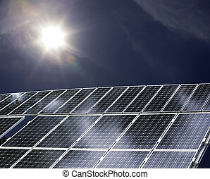 solar power - detail of a solar power plant with sun shining...