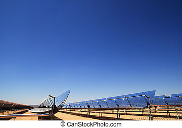 side view of SEGS solar thermal energy desert electricity plant with parabolic mirrors concentrating the sunlight with blue sky copy space