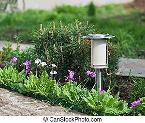 Solar-powered lamp on garden background.
